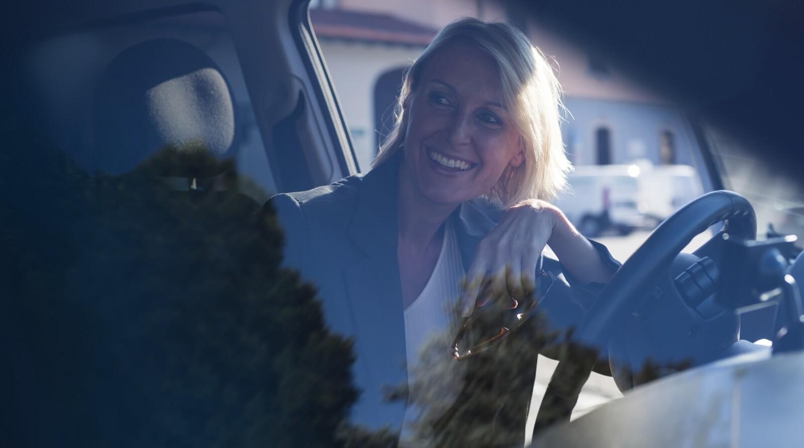 Lächelnde Frau im Auto hinter dem Lenkrad