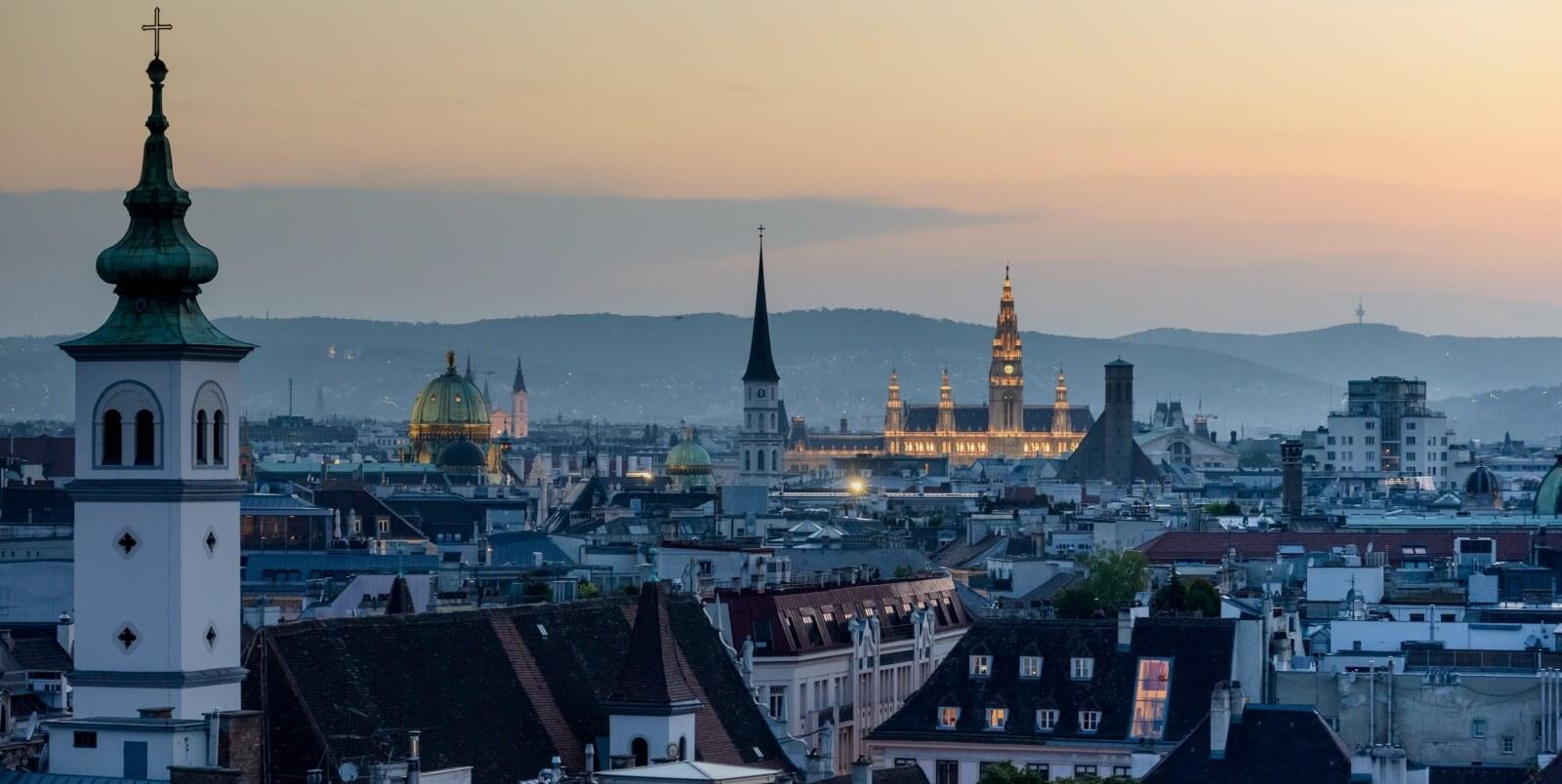 Blick über die Dächer von Wien in Richtung Rathaus bei Dämmerung