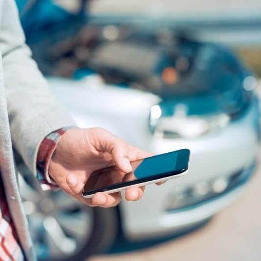 Legerer Geschäftsmann steht beim parkenden Auto und hält ein Handy in der Hand
