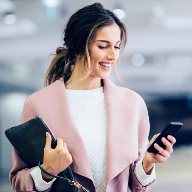 Geschäftsfrau mit dunklen Haaren und rosa Mantel, hält Handy in der Hand und Laptop unterm Arm