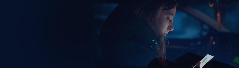 Frau im Auto sitzend, blickt auf Mobiltelefon