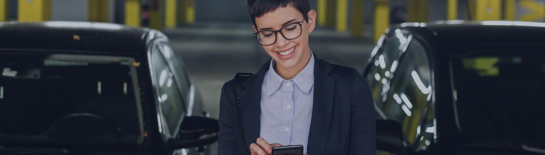 Frau mit Brille und Mobiltelefon in der Hand in einer Tiefgarage