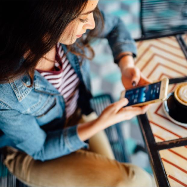 Frau in Freizeitkleidung blickt auf Mobiltelefon